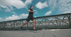 Jogger running over Bridge with moving train in background Stock Footage