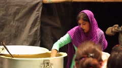 Young woman serves vegetarian food to hungry flood victims Stock Footage