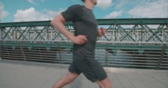 Runner jogging over The Golden Jubilee Bridge, London. Stock Footage