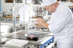 Professional chef adding pepper on steak in the kitchen Stock Photos