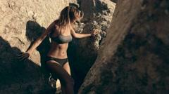 Attractive model posing between rocks Stock Footage