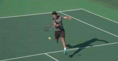 Tennis Player Powerfully Volleys Ball over Net. Stock Footage