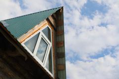 Triangular skylight of an attic of a village log house under construction aga - stock photo