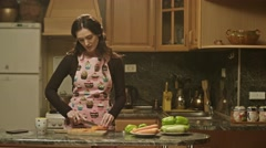 Woman cooking and slicing vegetables in kitchen. Shot on RED EPIC Cinema Camera. Stock Footage