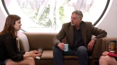 A professor sits in a study room and talks with two of his students Stock Footage