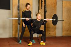 Personal trainer assisting in the squat exercise - stock photo