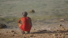 The rear view of a young black man, sitting on his haunches on the beach and Stock Footage