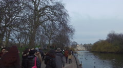 People passing by the lake at St. James park Stock Footage