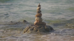 The pyramid of small stones standing in the water - stock footage