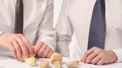 Businessmen building pyramid at the workplace - stock footage