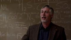 A professor standing in front of a chalkboard with equations written on it Stock Footage