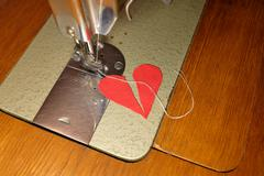 Tailor try to sew two halves of broken heart Stock Photos