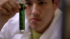 Rack focus of a young man in a lab coat inspecting a liquid in a test tube Stock Footage