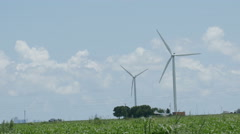 Windmill wind turbine with trucks driving by Stock Footage