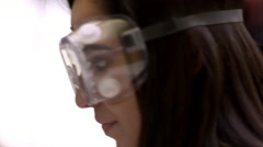 Close up of a young woman wearing safety goggles and smiling Stock Footage