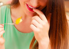 Woman eating cream cake with fruits. Gluttony. Stock Photos