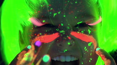 Kids having fun and painting their faces with neon paint Stock Footage