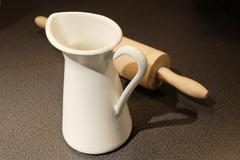 Kitchen Utensil, White Ceramic Milk Jug with Rolling Pin Used to Make Bakery - stock photo