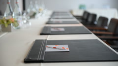 Rack focus along notepads on conference table Stock Footage