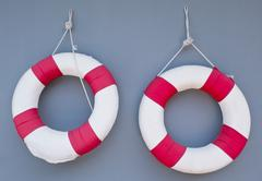 Stock Photo of Two Red Life Buoy Hanging on A Grey Concrete Wall for Swimming Pool Isolated