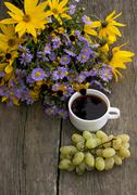 bouquet of wild flowers, coffee and grapes, top view, still life - stock photo