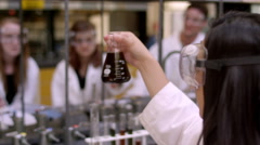 A student holding up a beaker during class in a science lab - stock footage