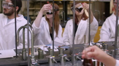 Students in a science lab observing a liquid in their beakers Stock Footage