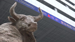 Bull statue in front of a ticker board at the Shenzhen stock exchange, China Stock Footage