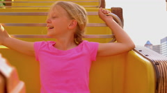 A little girl riding a carnival ride, holding on tight and looking scared - stock footage