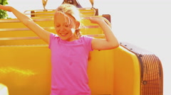 A little girl riding a carnival ride, screaming and putting her hands in the air Stock Footage