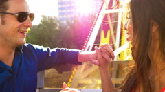 An attractive couple laughing and holding hands on a ferris wheel Stock Footage
