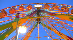 View from below of a carnival ride operating at night, with colorful lights - stock footage