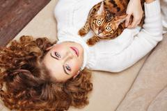 Stock Photo of Girl and a cat lying on the couch.