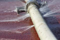 Wasting water - water leaking from hole in a hose Stock Photos