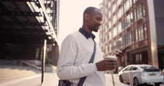 African American businessman walking through city using smart phone Stock Footage