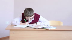 Boy with glasses writes in a notebook sitting at a desk Stock Footage