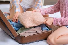Stock Photo of Two sisters are packing baggage