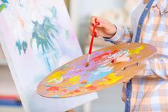 Young girl is busy oil-painting - stock photo