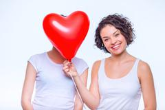 One lady hides her sisters face behind balloon - stock photo