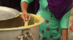 Young woman serves vegetarian food to hungry flood victims, mid shot Stock Footage