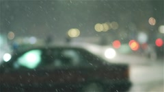 Snow fall in slow motion at night over city street Stock Footage