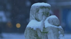 Snow falls in slow motion of the monument of a woman cradling a toddler Stock Footage