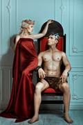 Man sits on the throne and looks at queen. - stock photo