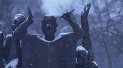 Snow falls in slow motion over art monument of man Stock Footage