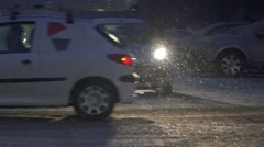 Car crosses the avenue at night with heavy snowfall in slow motion Stock Footage