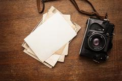 Old retro camera with photo on vintage grunge wooden boards Stock Photos