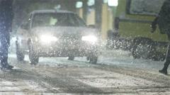 Heavy snowfall street illuminated by the headlights of the car pedestrians Stock Footage