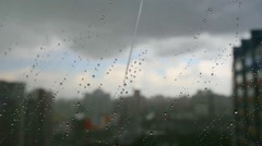 Urban view of rain drops falls on a window during a stormy day overlooking city Stock Footage