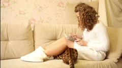 Girl playing on a tablet computer. Bengal cat. Pet. - stock footage
