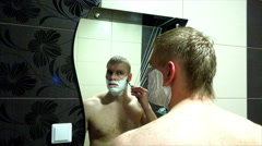 Man shaving machine tool before the mirror in the bathroom Stock Footage